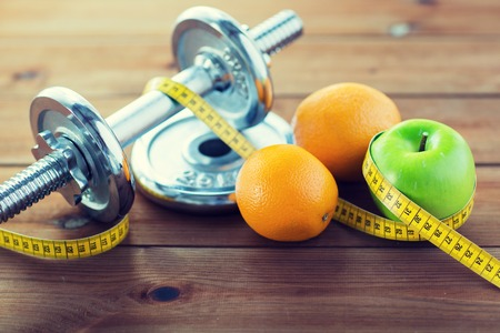 close up of dumbbell, fruits and measuring tape Stock Photo