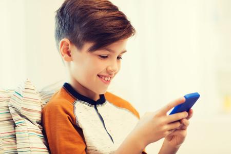 niños platicando: niño con los mensajes de texto de teléfonos inteligentes o jugar en casa