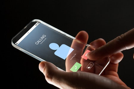 incoming: close up of hand with incoming call on smartphone Stock Photo
