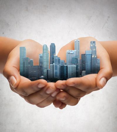 手の上に都市を置く灰色のコンクリート背景