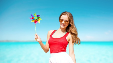 happy woman with pinwheel over blue sky and sea Фото со стока