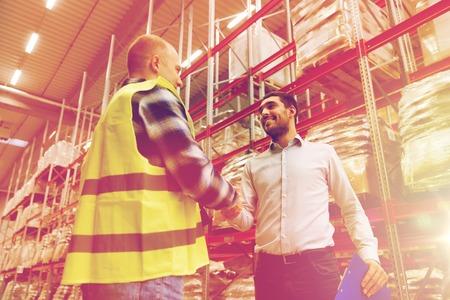 los trabajadores y hombres de negocios con el portapapeles en el almacén