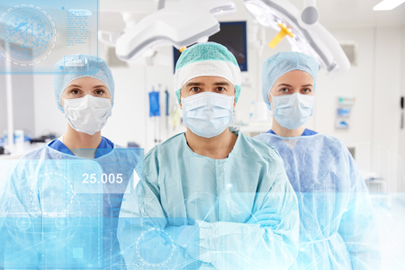 virtual assistant: group of surgeons in operating room at hospital Stock Photo