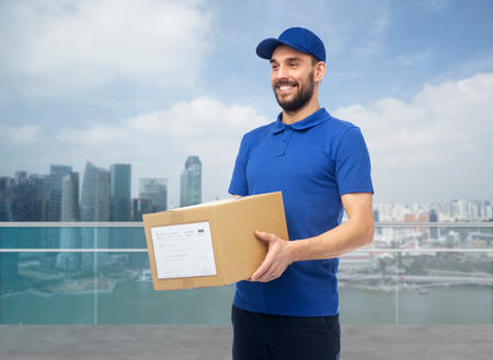 deliverer: happy delivery man with box over singapore city Stock Photo