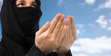 paranja: close up of praying muslim woman in hijab over sky Stock Photo