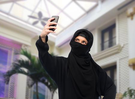 paranja: muslim woman in hijab taking selfie by smartphone