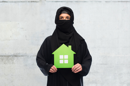 yashmak: muslim woman in hijab with green house over white