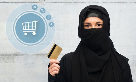 paranja: muslim woman in hijab with credit card over white