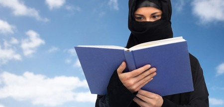 paranja: muslim woman in hijab reading book over sky