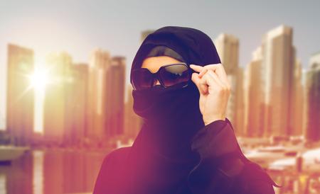 paranja: muslim woman in hijab and sunglasses in dubai city