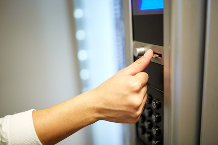 hand inserting euro coin to vending machine