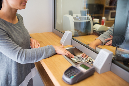 cash on hand: clerk giving cash money to customer at bank office Stock Photo