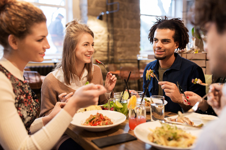 Amis heureux manger et boire au restaurant Banque d'images - 72886226