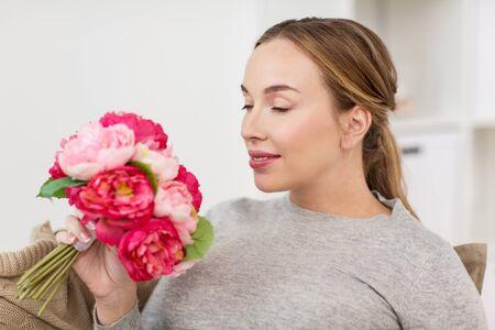 olfato: mujer feliz con olor de flores en el hogar Foto de archivo