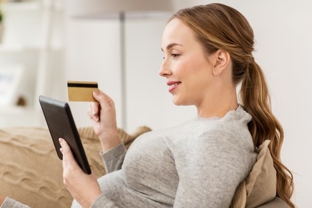 donna incinta con tablet pc e carta di credito