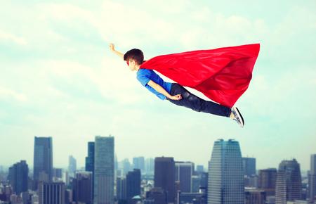 想像力、自由、子供の頃、動き、人々 のコンセプト - 赤いスーパー ヒーロー マントとマスク街背景空気で飛んでの少年
