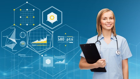 smiling female doctor or nurse with clipboard Stock Photo