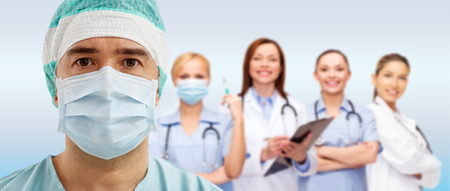 surgeon in mask with group of medics over blue photo