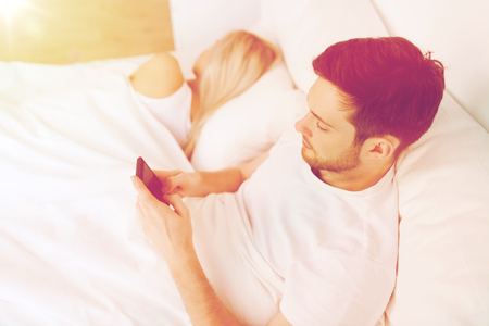 man texting message while woman is sleeping in bed 版權商用圖片 - 72947718