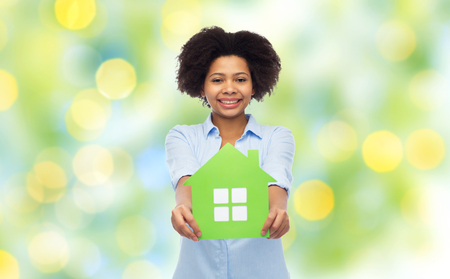 happy african american woman with green house icon Stock Photo