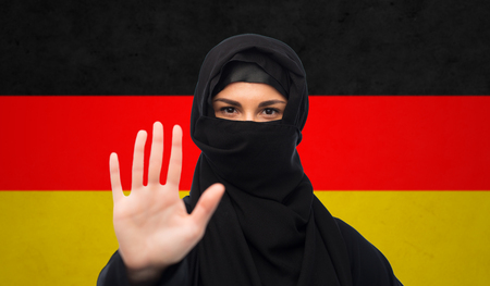 yashmak: muslim woman in hijab showing stop sign