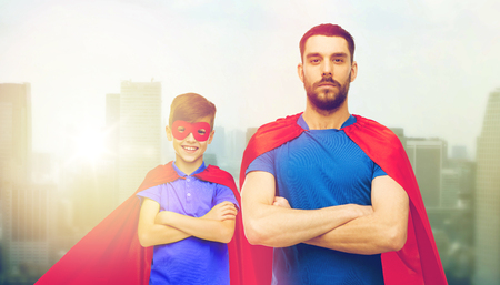 man and boy wearing mask and red superhero cape Stock Photo