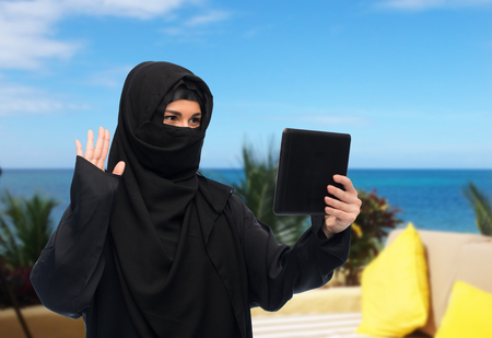 yashmak: muslim woman in hijab with tablet pc having chat Stock Photo