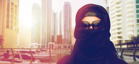 paranja: muslim woman in hijab and sunglasses at dubai city
