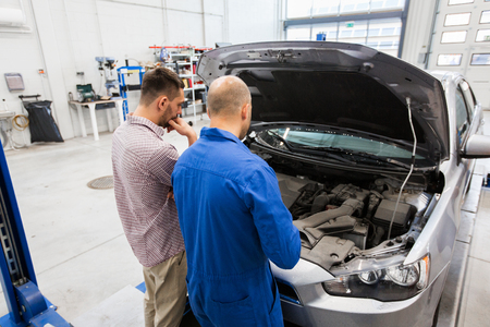 auto mechanic and man or car owner at workshop Stock Photo