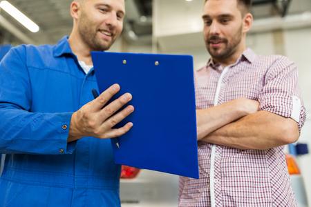 Automechaniker mit Zwischenablage und Mann im Autogeschäft Standard-Bild - 72947787