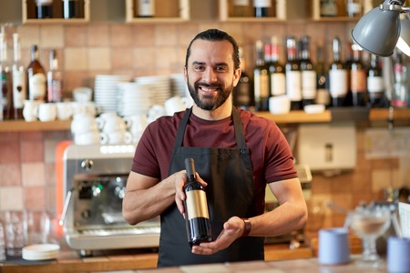 aperitive: happy man or waiter with bottle of red wine at bar Stock Photo