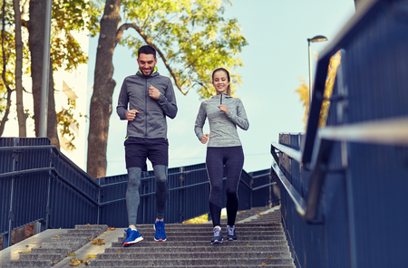 tracksuit: happy couple running downstairs in city Stock Photo