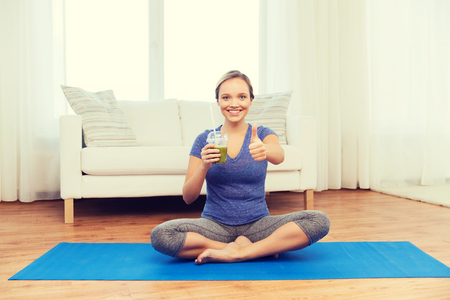 woman diet: woman with smoothie showing thumbs up at home