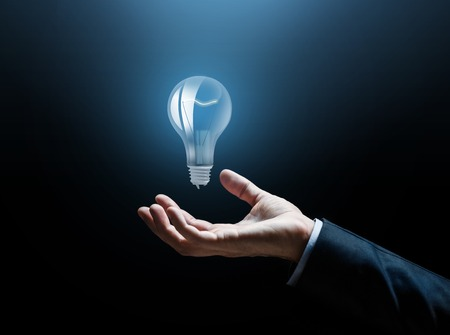 close up of businessman hand with light bulb