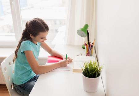 gelukkig meisje met boek schrijven naar notebook thuis