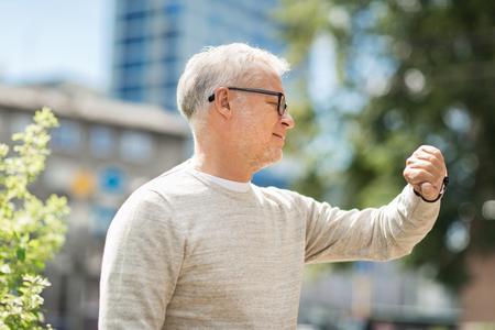 puntualidad: Hombre mayor tiempo en su reloj de pulsera de comprobación Foto de archivo