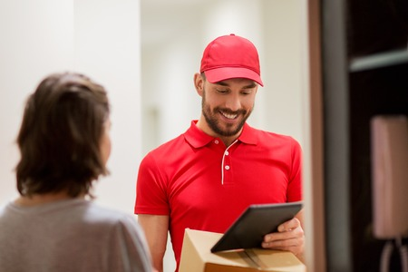 addressee: deliveryman with tablet pc and box at customer