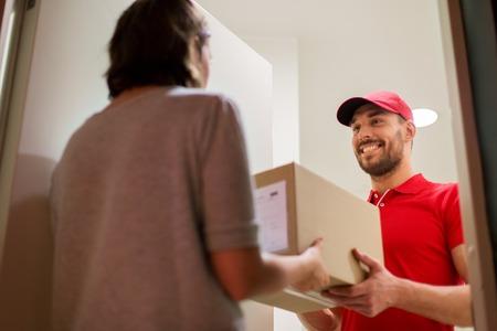 Uomo di consegna felice che dà il contenitore pacco cliente Archivio Fotografico - 73233765