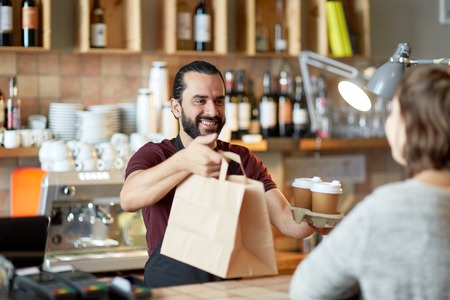 コーヒー ショップで男やウェイターのサービング顧客
