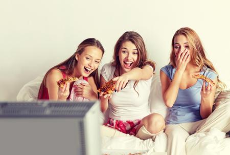 amigos felices comiendo pizza y viendo la televisión en casa Foto de archivo
