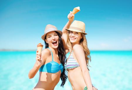 glimlachende vrouwen eten van ijs op het strand Stockfoto