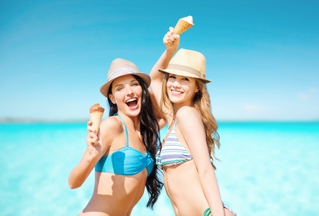 smiling women eating ice cream on beach Imagens