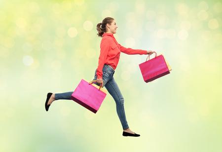 実行している買い物袋を持つ笑顔の若い女性