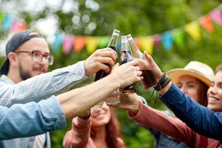 clinking: happy friends clinking glasses at summer garden Stock Photo