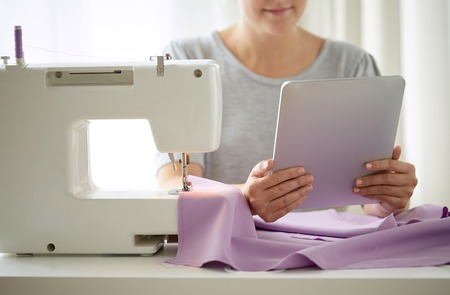 tailor with sewing machine, tablet pc and fabric Stock Photo