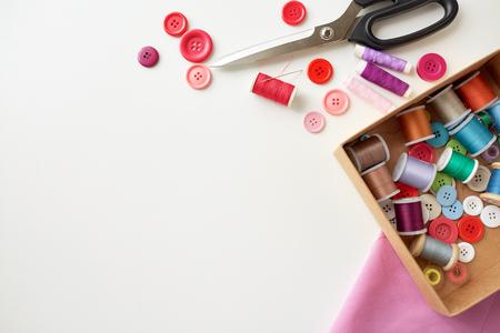 Kasten mit Fadenspulen und Nähknöpfen am Tisch Standard-Bild - 73360080