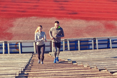 upstairs: happy couple running upstairs on stadium