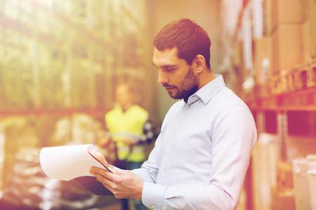 groothandel, logistiek, mensen en export concept - zakenman of supervisor met klemborden bij pakhuis