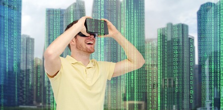 mediated: modern technology, cyberspace, entertainment and people concept - happy young man with virtual reality headset or 3d glasses over city skyscrapers and binary code background Stock Photo