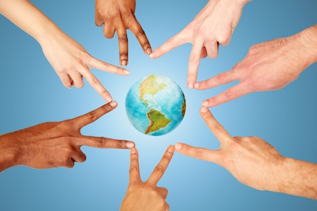 demografia: día de la tierra, la diversidad, la etnia, el concepto de las personas internacionales - grupo de manos que muestran la paz muestra de la mano sobre el fondo azul y el planeta Foto de archivo